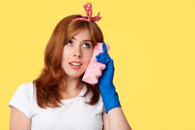 Domestic work concept. pretty young busy housewife pretends communicate via smart phone, uses sponge Free Photo