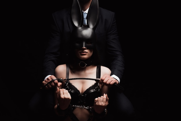Dominant man with a flogger whip and a submissive girl in underwear wearing a mask and handcuffs Premium Photo