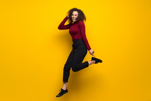 Dominican woman with curly hair jumping over isolated yellow wall Premium Photo