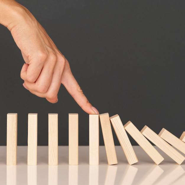 Игра в домино из деревянных элементов, олицетворяющих финансовую борьбу Бесплатные Фотографии
