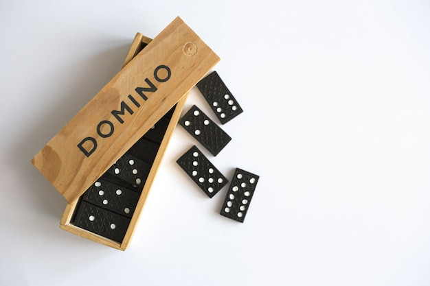 Domino game in wooden box on white background, top view. family board game Premium Photo