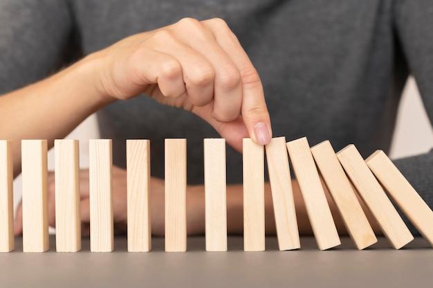 Domino realizzato con pezzi di legno che rappresentano le finanze Foto Gratuite