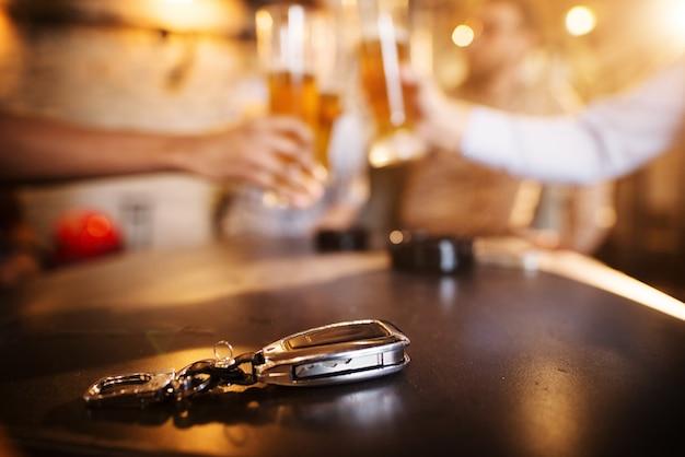 飲酒運転しないでください!ビールとチリンとぼやけている友人の前で木製のパブのテーブルに車のキー。 Premium写真