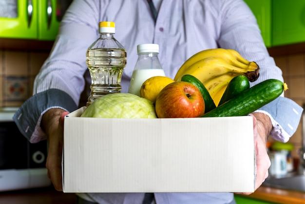 募金箱の食品配達食品寄付のコンセプトです。野菜、果物、その他の食べ物が入った募金箱を持っている人 Premium写真