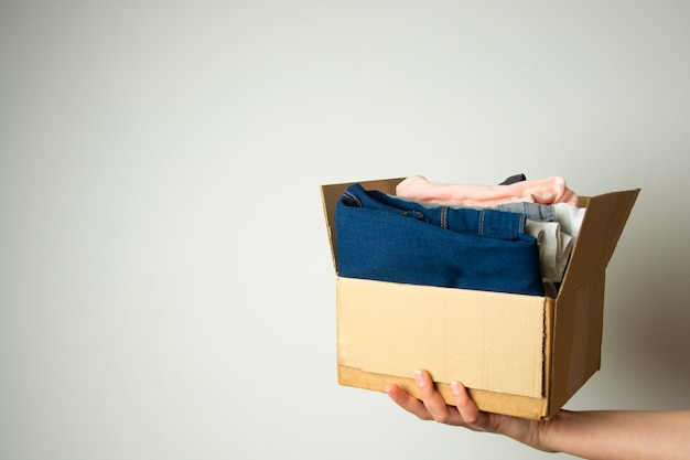 Donation concept. hands holding donate box with clothes. copy space. Premium Photo