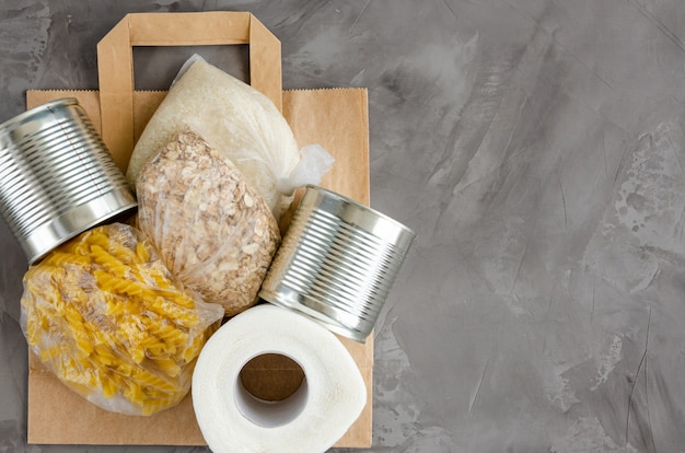 Donation food. paper bag with canned food, pasta, oatmeal, rice and toilet paper on a dark concrete background. food delivery. horizontal, top view, copy space. Premium Photo