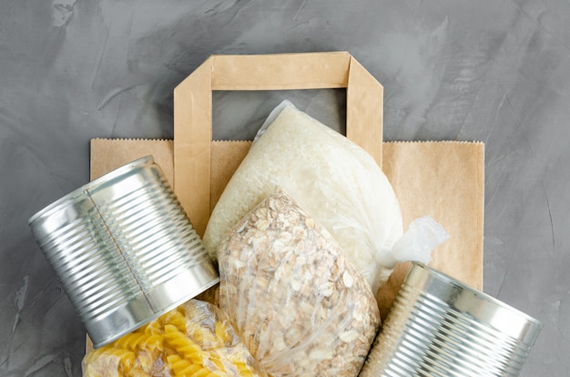 Donation food. paper bag with canned food, pasta, oatmeal, rice and toilet paper on a dark concrete background. food delivery. Premium Photo