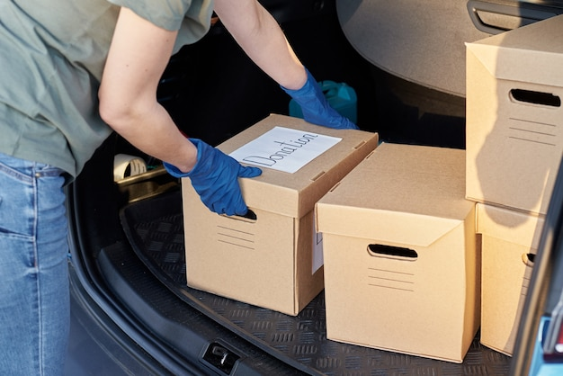Donation and volunteering concept. woman in gloves load box in car trunk. Premium Photo