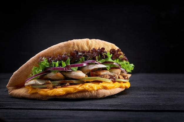 Донер кебаб - жареное куриное мясо с овощами в лаваше Premium Фотографии