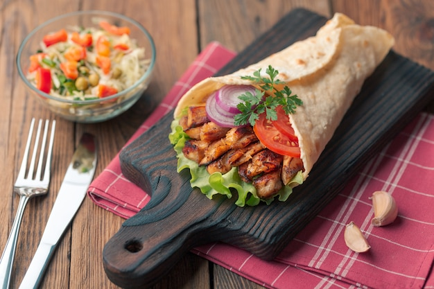 Doner kebab is lying on the cutting board. shawarma with chicken meat, onions, salad lies on a dark old wooden table. Premium Photo