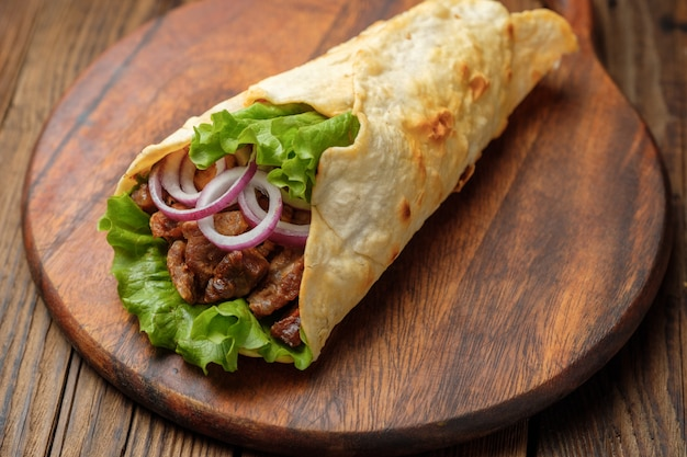 Doner kebab is lying on the cutting board. shawarma with meat, onions, salad lies on a dark old wooden table. Premium Photo