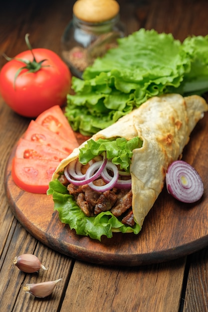Doner kebab is lying on the cutting board. shawarma with meat, onions, salad lies on a white old wooden table. Premium Photo