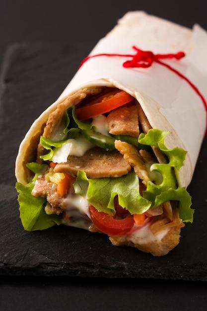黒いスレートにドネルケバブまたはシャワルマサンドイッチをクローズアップ Premium写真