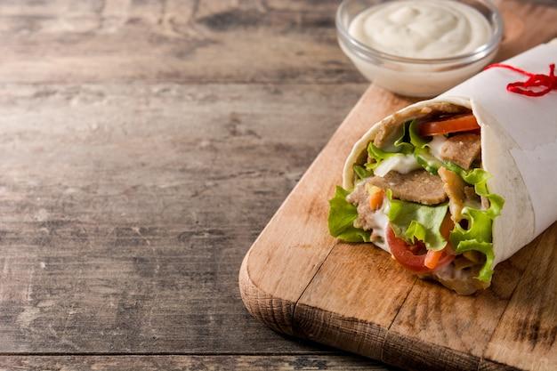 Донер кебаб или шаурма сэндвич на деревянный стол копией пространства Premium Фотографии