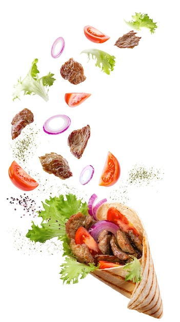 Doner kebab or shawarma with ingredients floating in the air : beef meat, lettuce, onion, tomatoes, spice. Premium Photo