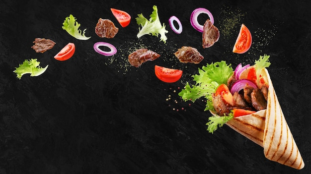 Doner kebab or shawarma with ingredients floating in the air  beef meat, lettuce, onion, tomatos, spice. Premium Photo