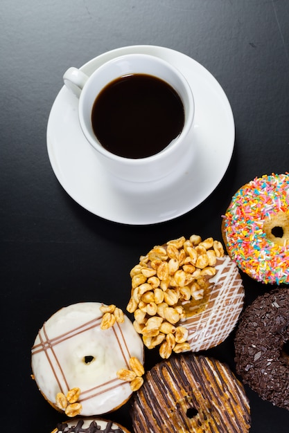 Donut and coffee on the black background Premium Photo