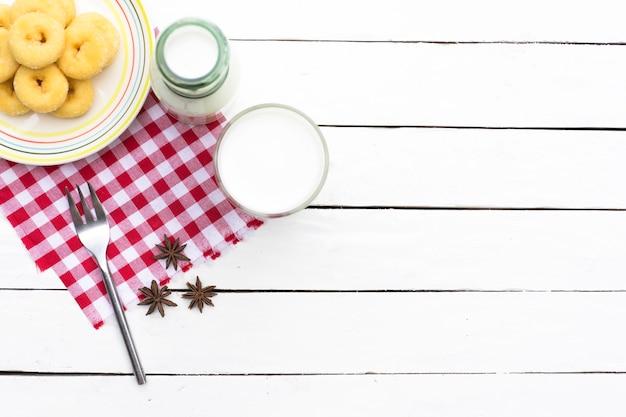 ドーナツのデザートとミルクボトルとミルクグラスのレッドチェッカー Premium写真