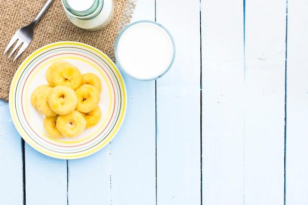 木製の空の青のテーブルにドーナツのデザートと牛乳瓶とミルクガラス。 Premium写真