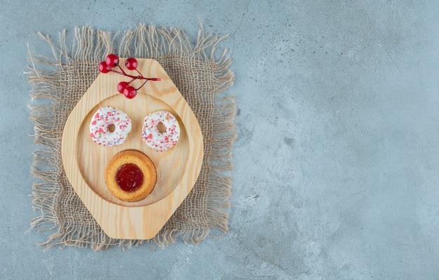 大理石の背景に木製の大皿にドーナツとゼリー入りケーキ。高品質の写真 無料写真