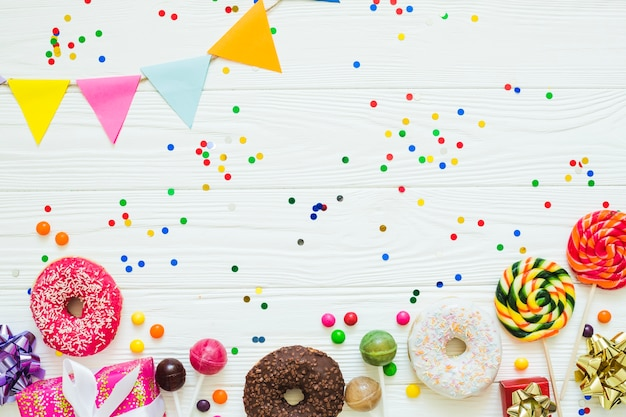 Donuts and candies with confetti Free Photo