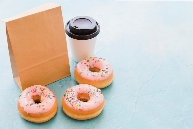 Donuts near package and disposal cup on blue background Free Photo