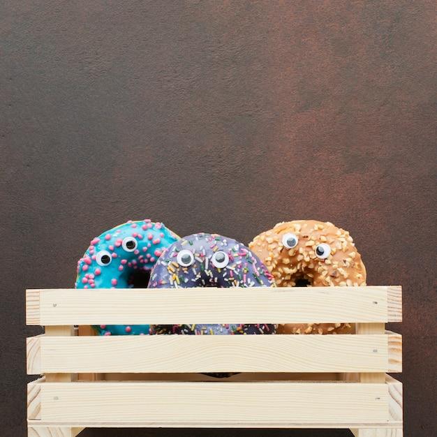 Пончики с глазами в деревянной коробке Бесплатные Фотографии