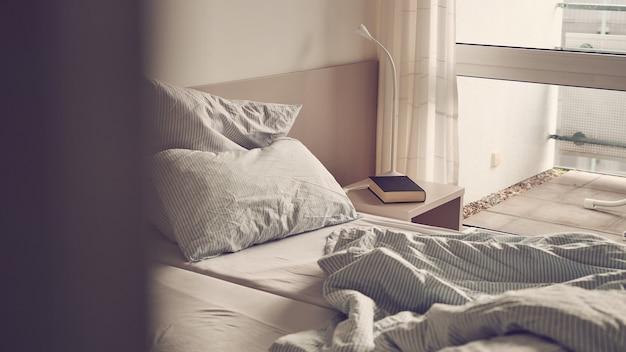 Дверь комнаты приоткрытая, с неубранной кроватью Premium Фотографии