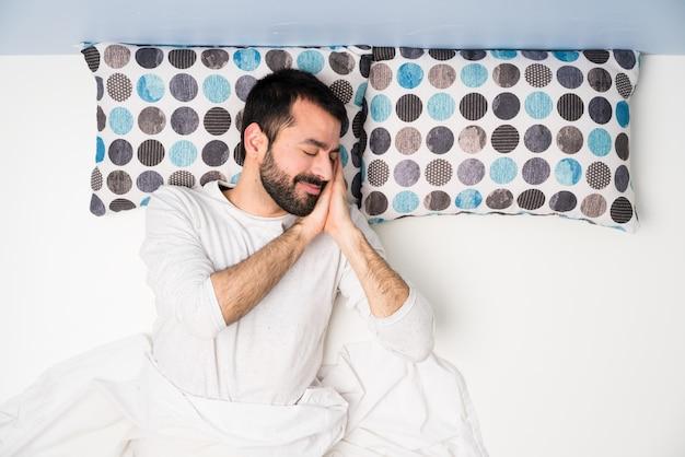Человек в постели в вид сверху, делая жест сна в dorable выражении Premium Фотографии