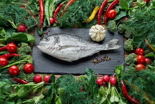 Dorada fish and green vegetables around on old wooden table. top view, healthy food. Premium Photo