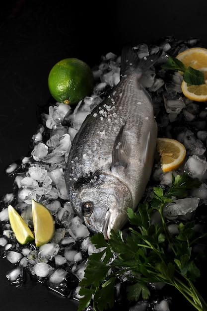Dorado fish lying on ice cubes, salt, parsley, lime and lemon Premium Photo