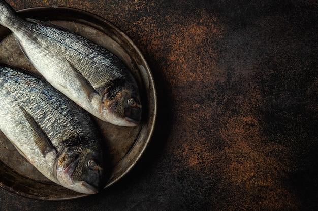 Dorado fish with ingredients on dark Free Photo