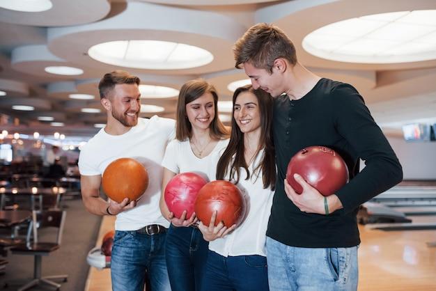 Doppio appuntamento. i giovani amici allegri si divertono al bowling durante i fine settimana Foto Gratuite