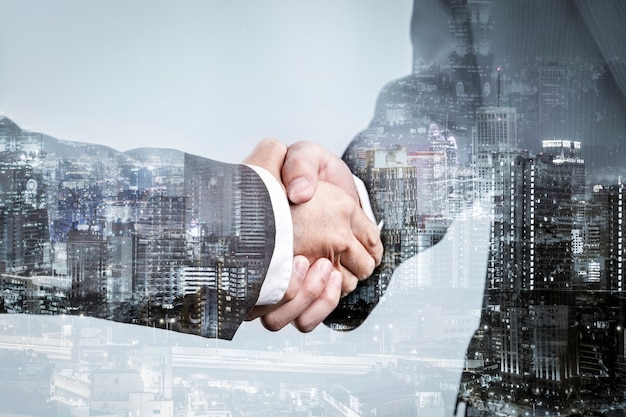 Double exposure of business partnership handshake and modern city , successful business greeting or agreement after perfect deal Premium Photo