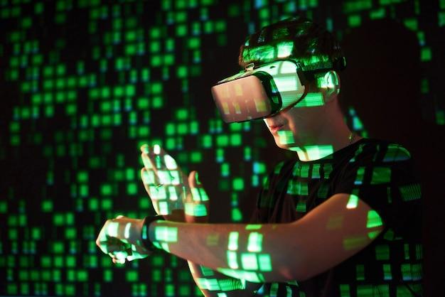 La doppia esposizione di un uomo caucasico e un visore vr per realtà virtuale è presumibilmente un giocatore o un hacker che inserisce il codice in una rete o server sicuro, con righe di codice in verde Foto Gratuite