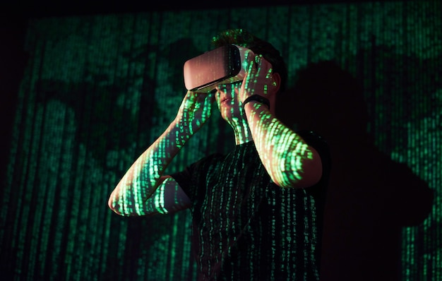 Double exposure of a caucasian man and virtual reality vr headset is presumably a gamer or a hacker cracking the code into a secure network or server, with lines of code in green Free Photo