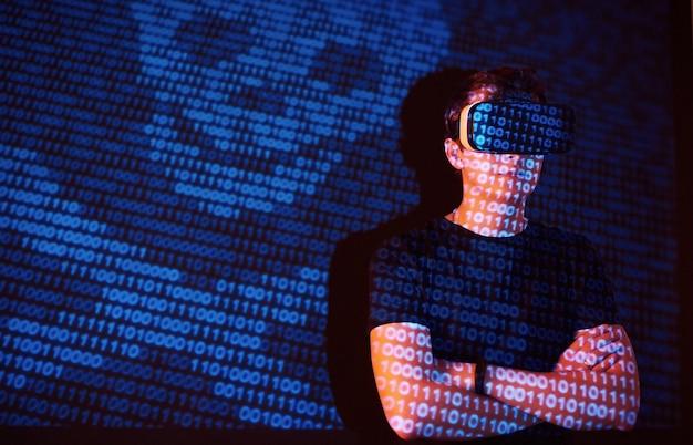 La doppia esposizione di un uomo caucasico e un visore vr per realtà virtuale è presumibilmente un giocatore o un hacker che cracka il codice in una rete o un server sicuro, con linee di codice Foto Gratuite
