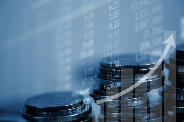 Double exposure of coin stack with stock market screen Premium Photo