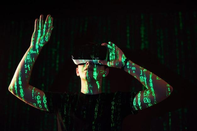 Двойное воздействие на кавказского человека и гарнитуру виртуальной реальности vr, предположительно, - это геймер или хакер, взламывающий код в защищенной сети или на сервере со строками кода, выделенными зеленым цветом. Бесплатные Фотографии