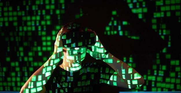白人男性とバーチャルリアリティvrヘッドセットの二重露出は、ゲーマーまたはハッカーがコードをセキュリティで保護されたネットワークまたはサーバーに侵入し、コードの行が緑色になっていることを示しています。 無料写真