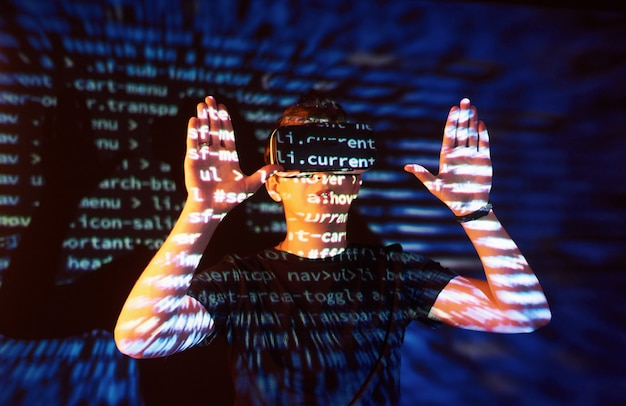 白人男性とバーチャルリアリティvrヘッドセットの二重露出は、ゲーマーまたはハッカーがコード行を使用して、安全なネットワークまたはサーバーにコードをクラックすることであると考えられます 無料写真