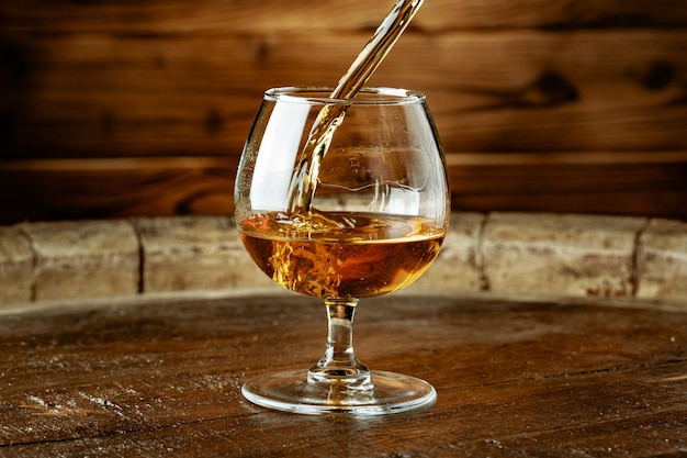 Double whiskey being poured into a glass Premium Photo