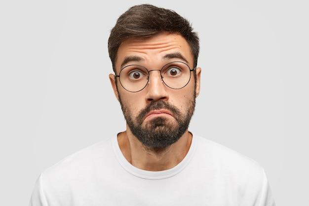 Сомневающийся бородатый мужчина нерешительно поджимает губы, испуганно смотрит в камеру, Бесплатные Фотографии