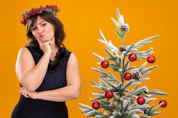 Сомнительная женщина средних лет в рождественском венке и гирлянде из мишуры на шее стоит возле украшенной елки Бесплатные Фотографии