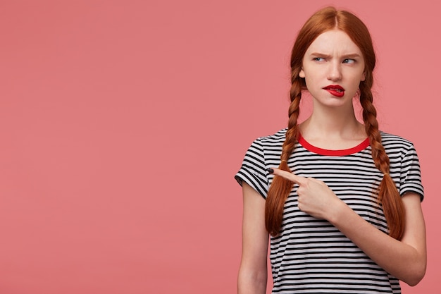 Doubtful thoughtful girl with two red haired braids biting red lip thinks about something, dressed in stripped t-shirt, looks to the upper left corner pointing fore finger isolated Free Photo