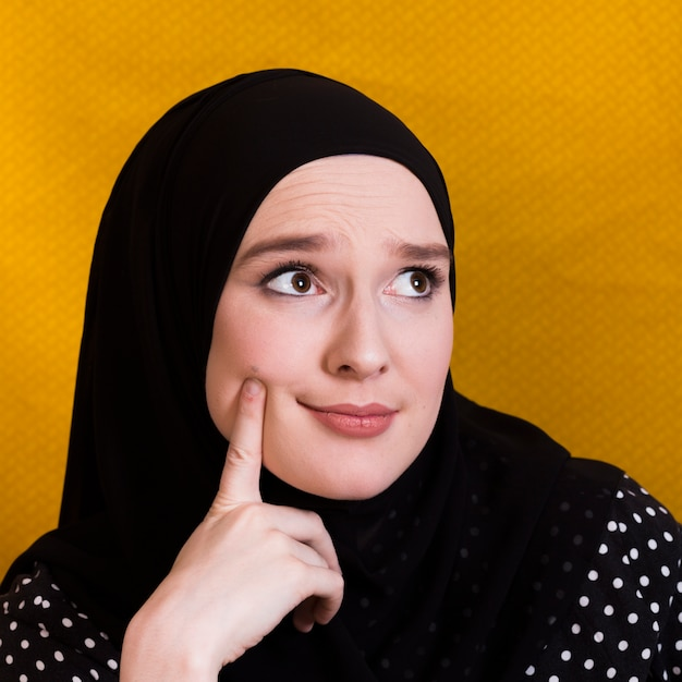 Doubtful woman thinking something with finger on her cheek Free Photo