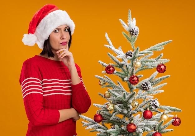 Сомнительная молодая девушка в шляпе санта-клауса, стоящая в профиле возле украшенной елки, держась за подбородок, глядя в камеру, изолированную на оранжевом фоне Бесплатные Фотографии