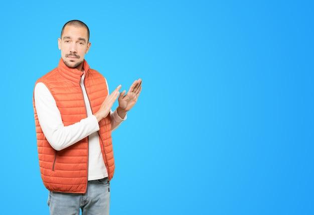 Сомнительный молодой человек делает жест спокойствия Premium Фотографии