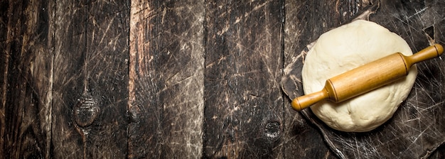 Фон из теста. свежее тесто со скалкой на деревянных фоне. Premium Фотографии