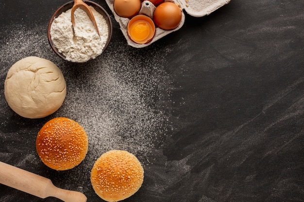 Dough and buns with flour and sesame seeds Free Photo